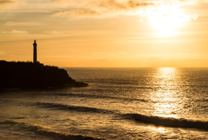 The sun setting over the Cape Hainsart lighthouse in Biarritz