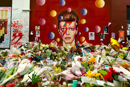 Flowers pile up outside the Bowie mural in Brixton