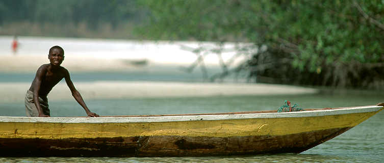 Boy fishing on canoe, Sierra Leone